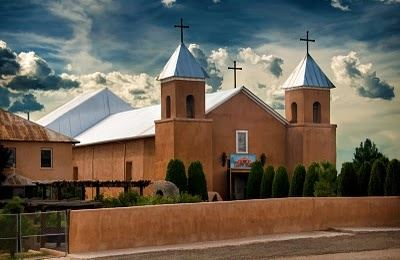 A modern day color image of the Santa Cruz Church with blue roofing and the preserved adobo walls